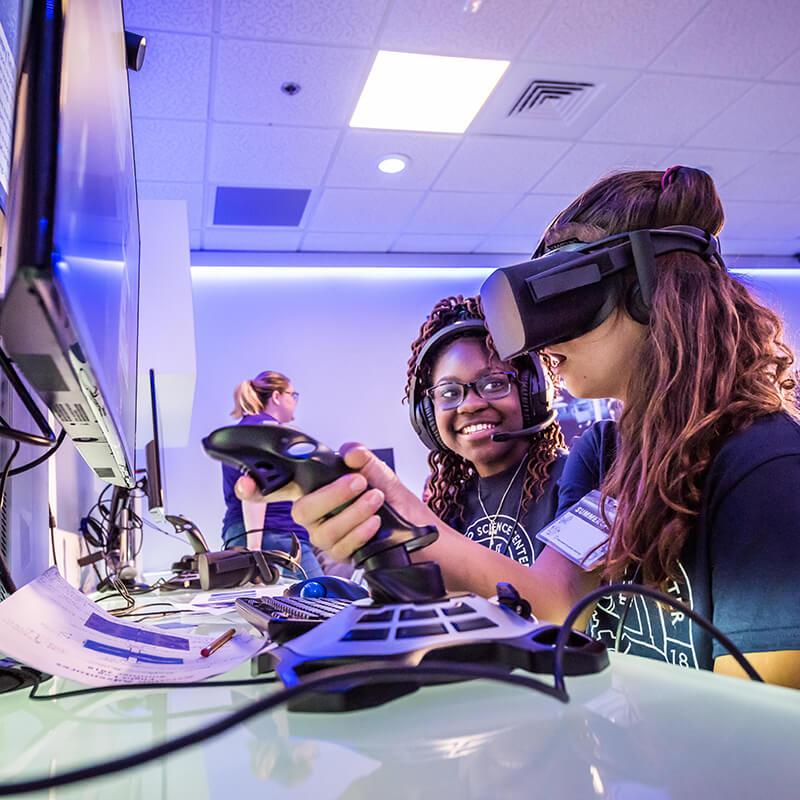 Girls experiencing virtual reality at Summer Academy.
