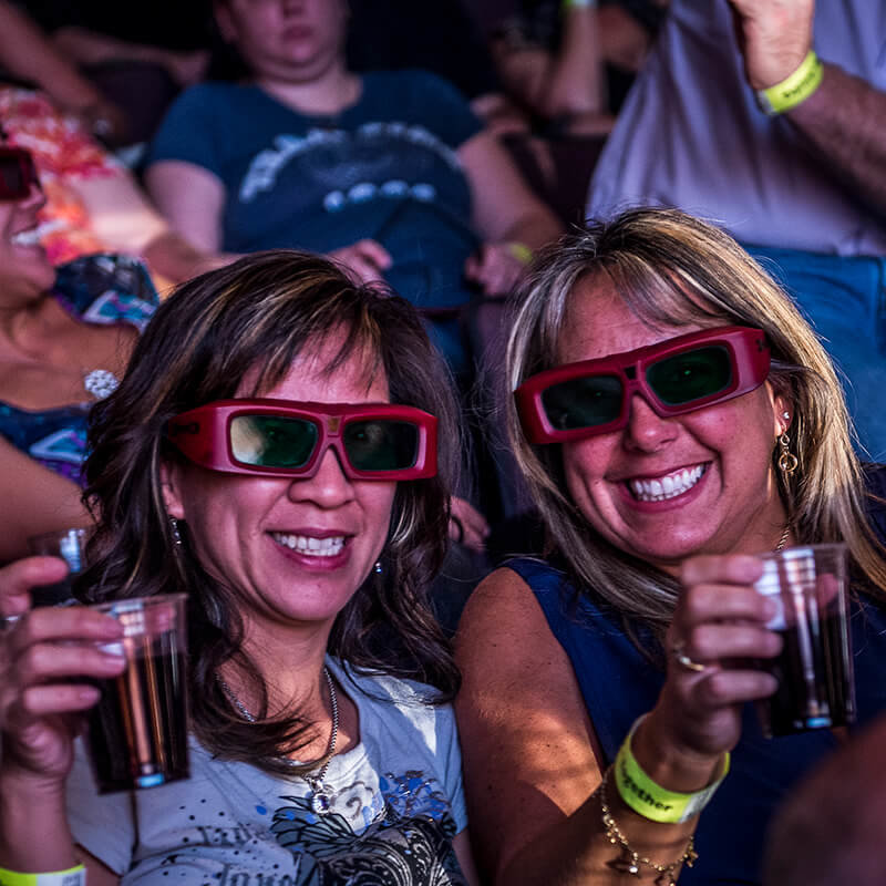Women wearing 3D glasses and toasting their beverages.