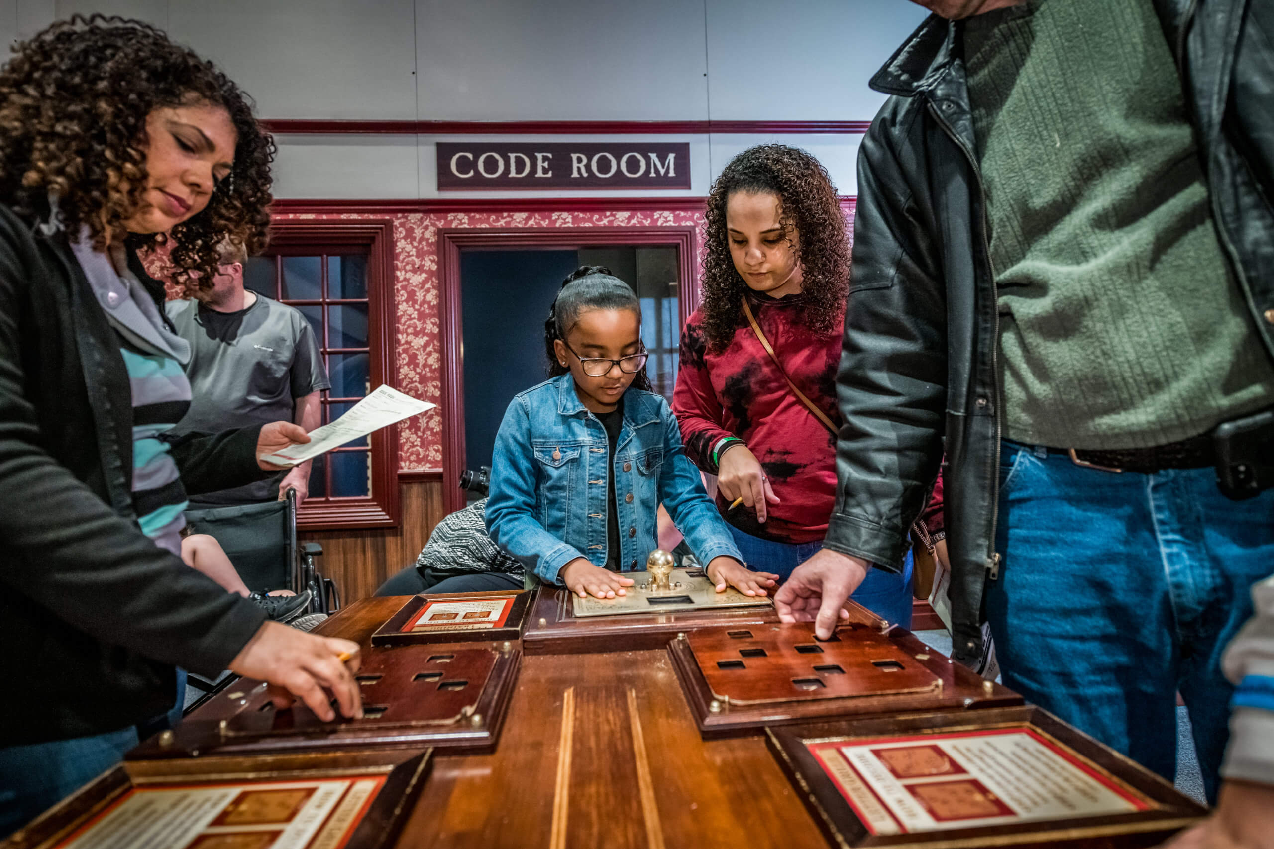 a group of people around a table solving a puzzle