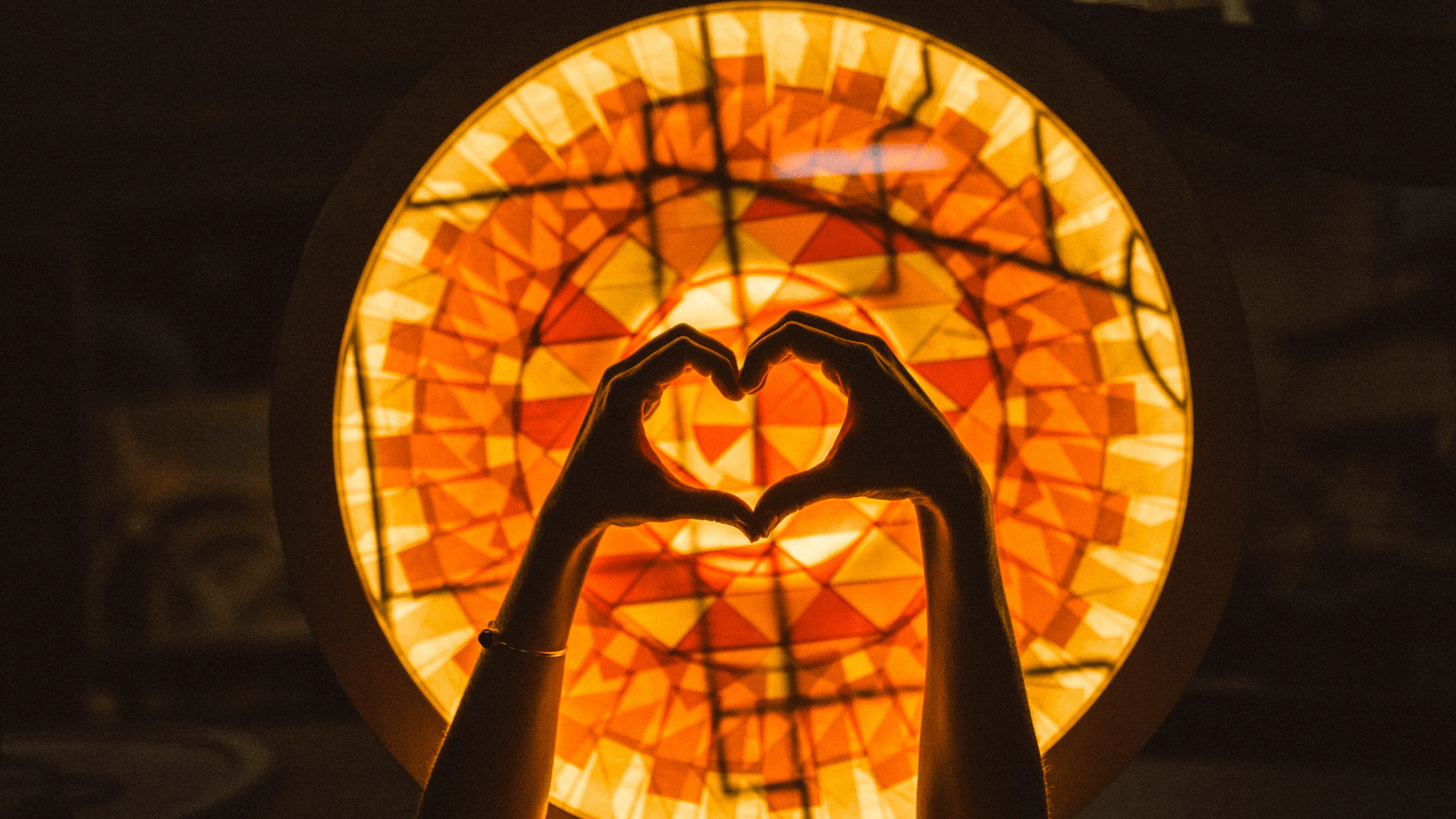 hands making a heart in front of backlit art