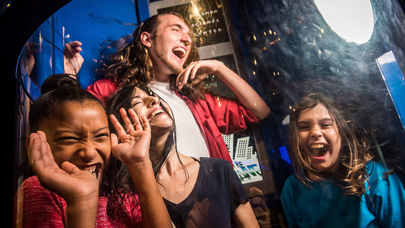 A group of guests laughing in the hurricane simulator.