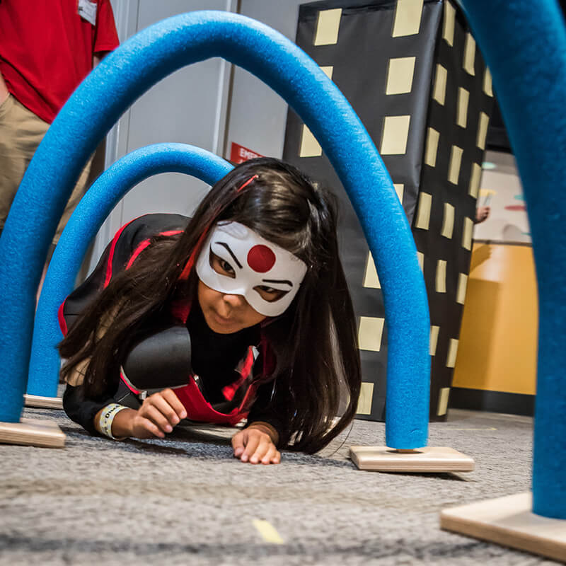 Child in superhero costume navigating obstacle course at Science Center
