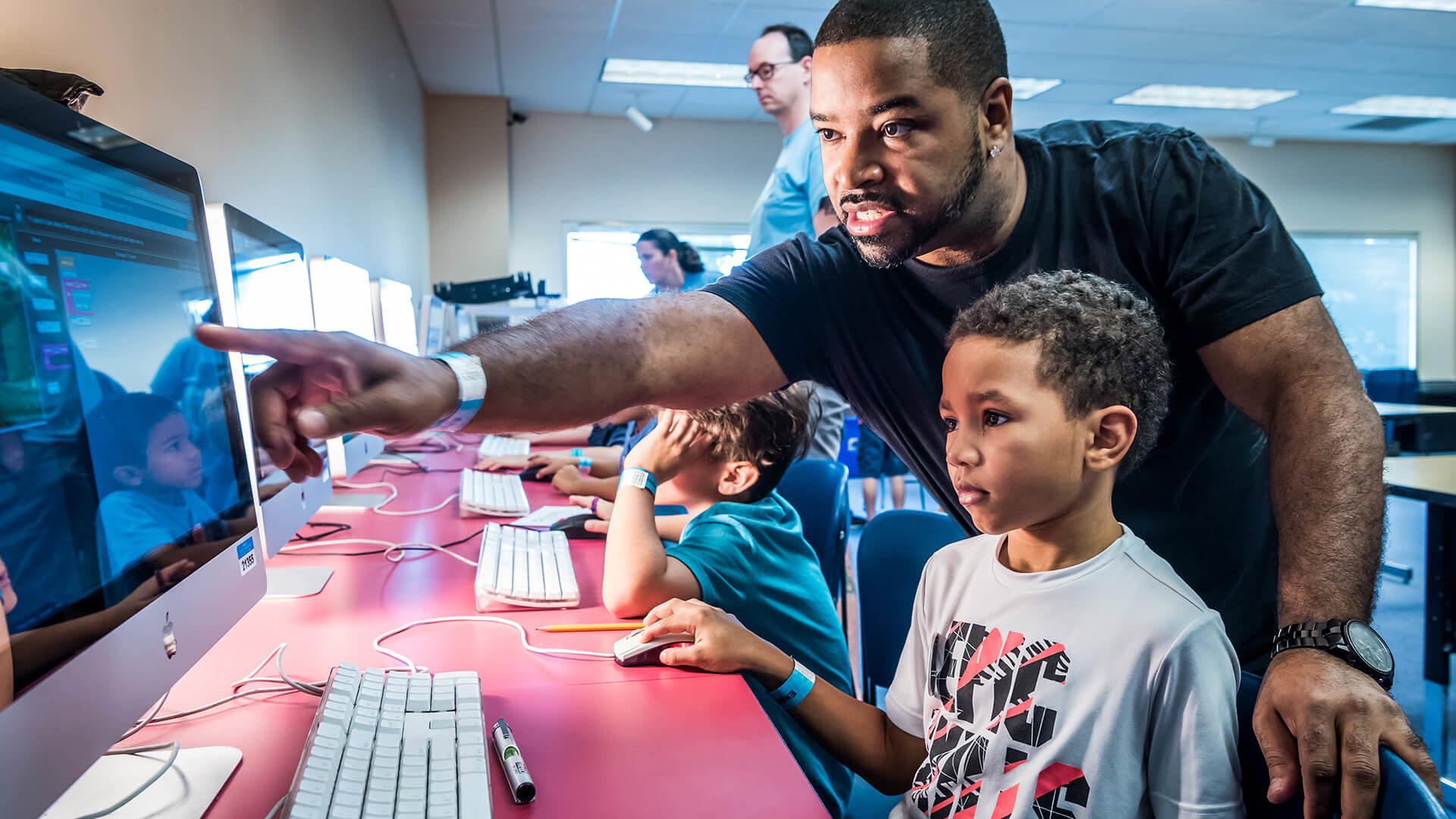 Image of educator and student pointing at a computer screen.