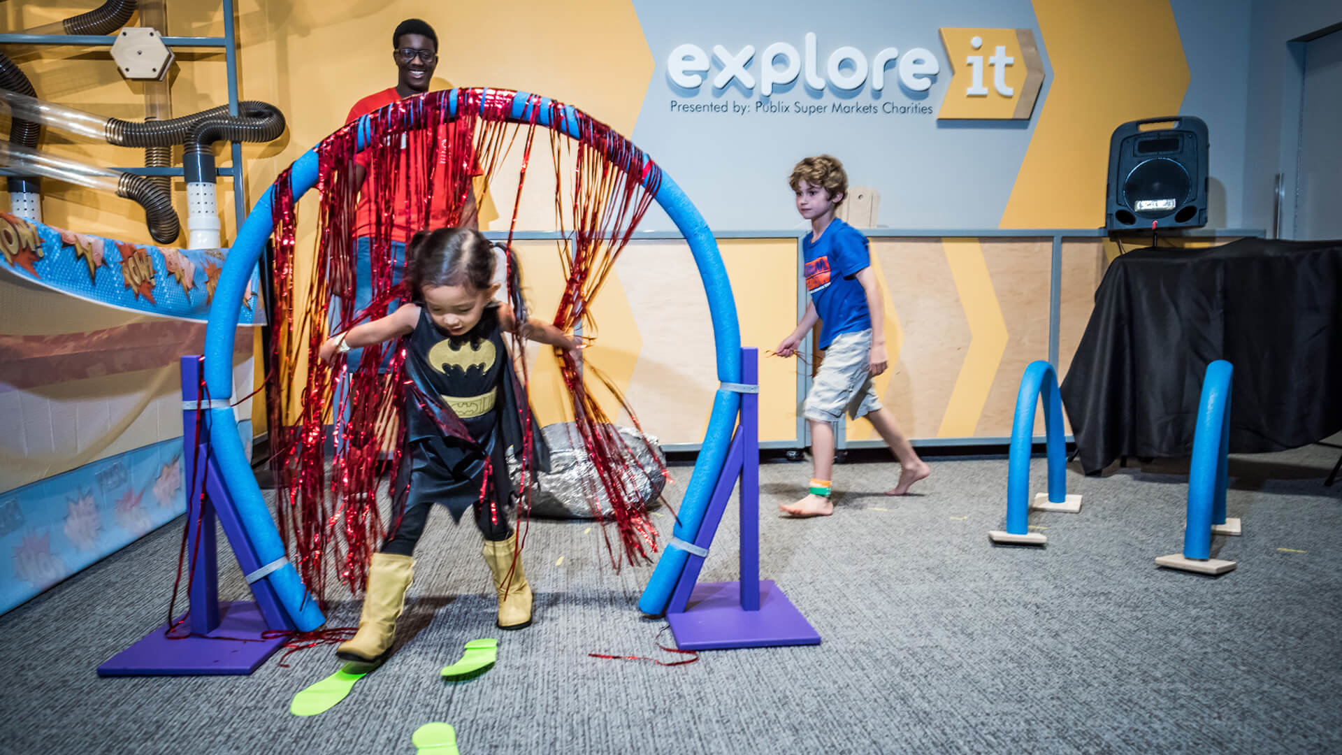 Child in Batgirl costume navigating obstacle course at Science Center