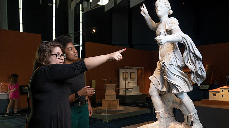 Two people pointing at a statue in Pompeii: the Immortal City exhibition.