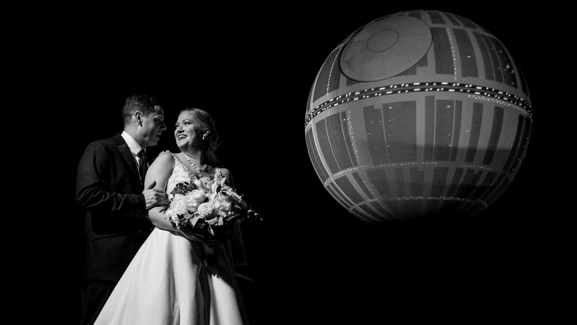 Black and white photo of newlywed couple posing in front of Death Star at their Orlando Science Center wedding
