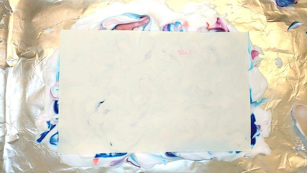 Place paper on shaving cream to create marbleized paper effect