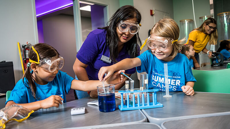 Two children in summer camp and an employee doing a chemistry experiment.