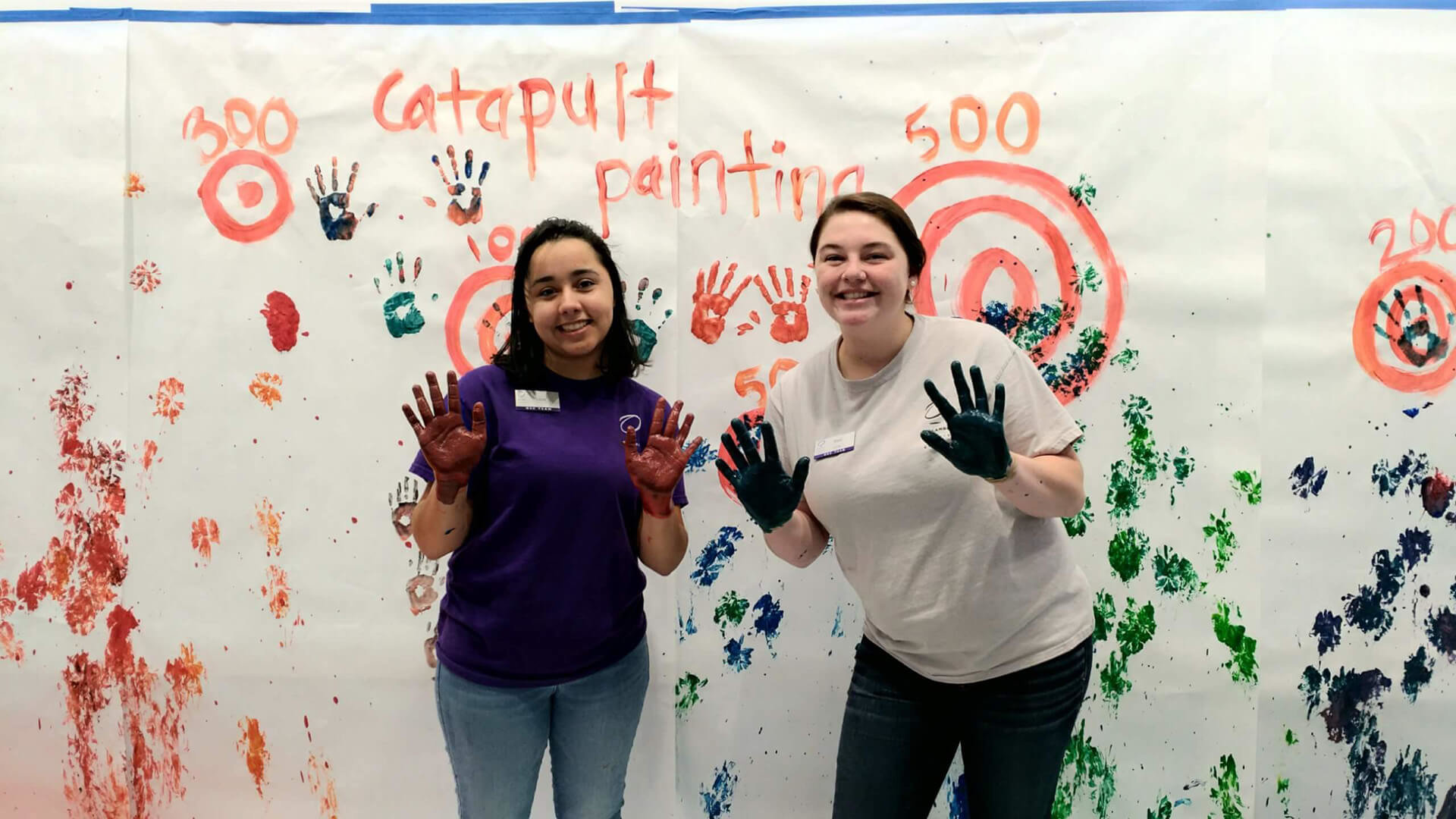 Two girls with paint everywhere on wall behind them.