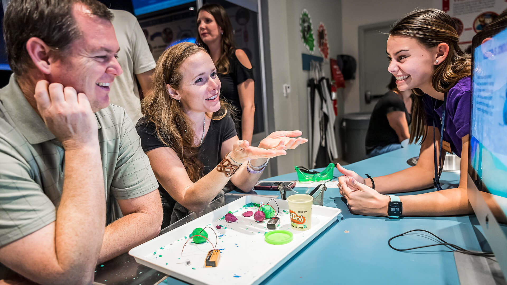 Two adult guests interactive with a staff member during a n electronics lab experiment in Dr. Dare's Lab.