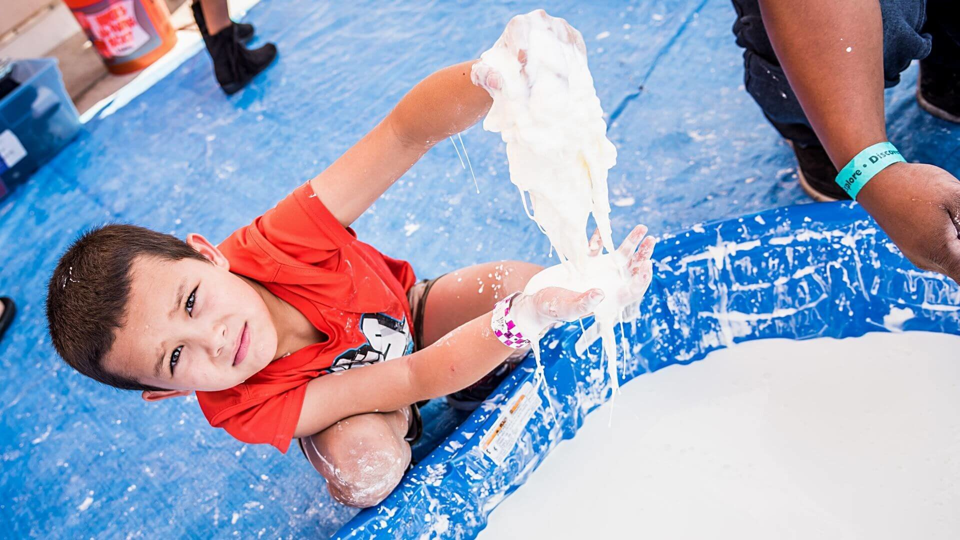 Child in red shirt doing STEM slime activity during Mess Fest at Orlando Science Center