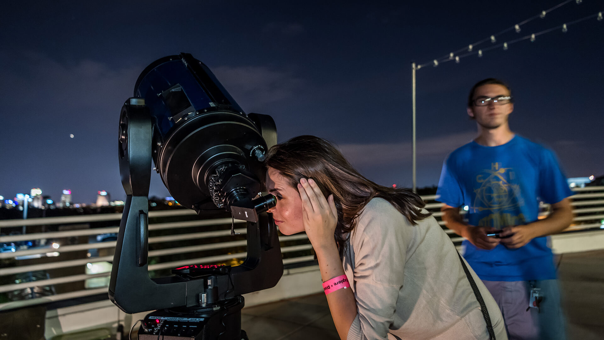 Guest stargazing through telescope outside on the Terrace at Orlando Science Center.