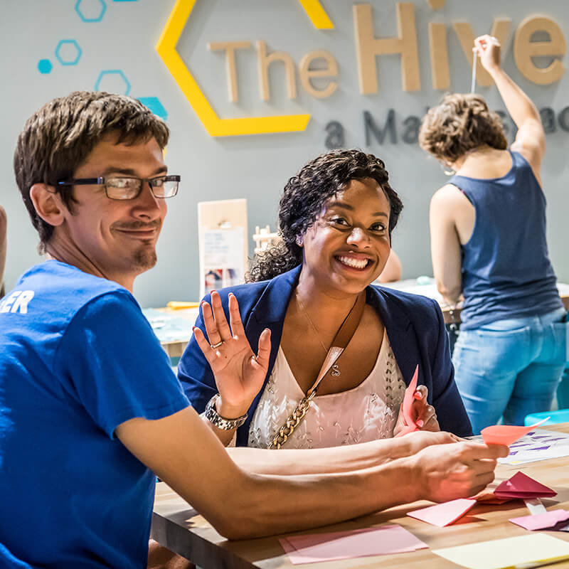 Guest and volunteer making origami in The Hive.