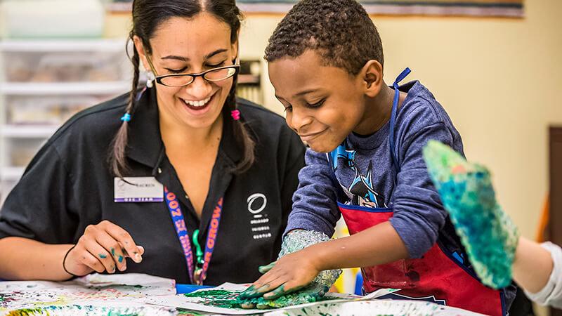 A teacher guides a preschooler in a finger paint activity.