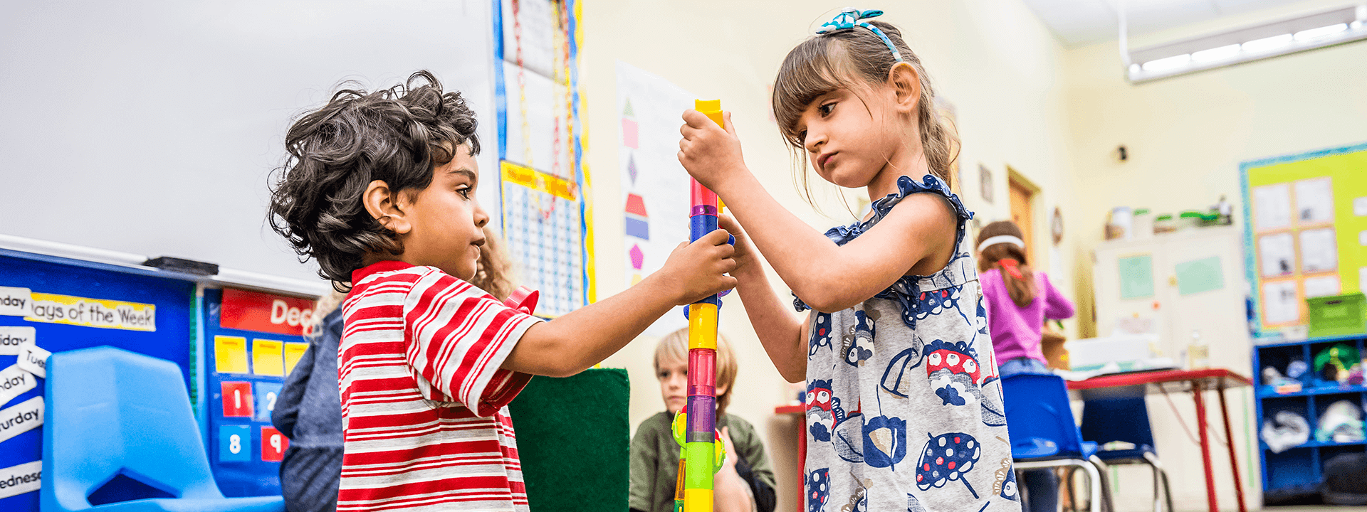 Two preschoolers build a tower together with small blocks.