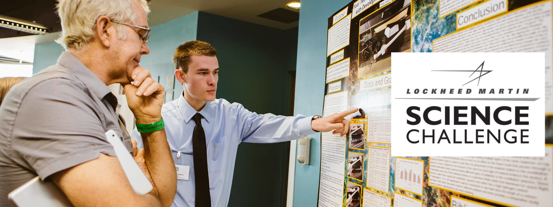 A high schooler explaining his research to a man at the Lockheed Martin Science Challenge.