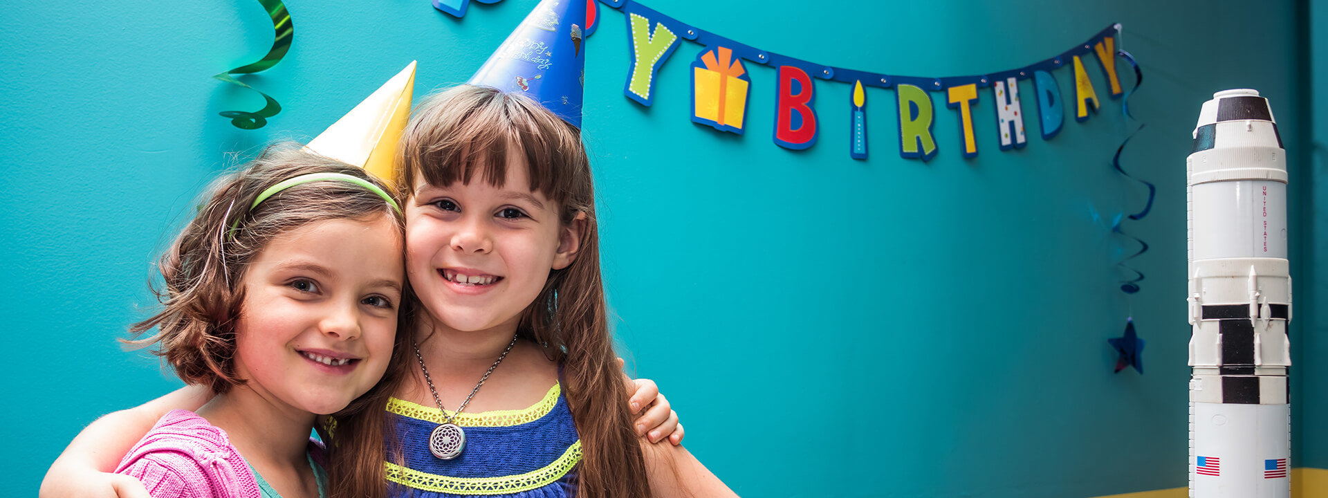Two young children smiling and hugging during a birthday party at Orlando Science Center.