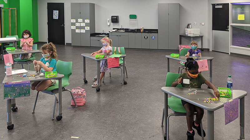Young children engaged in STEM activity at their desks in social distant camp classroom.