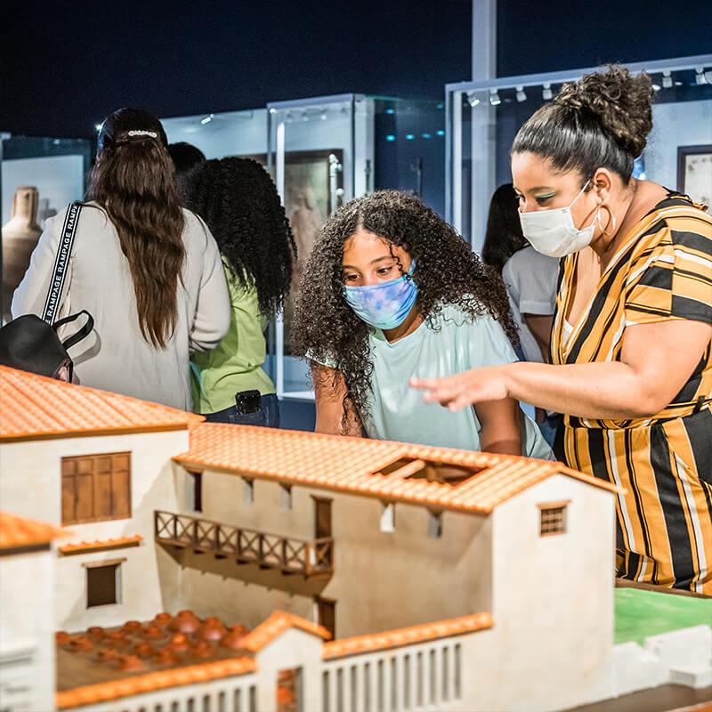 Child and caregiver exploring a model of a Pompeii villa.