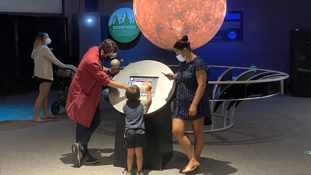 An OSC Science Program Interpreter shows a young child and caregiver the Science On A Sphere exhibit during a Guided Planet Tour.