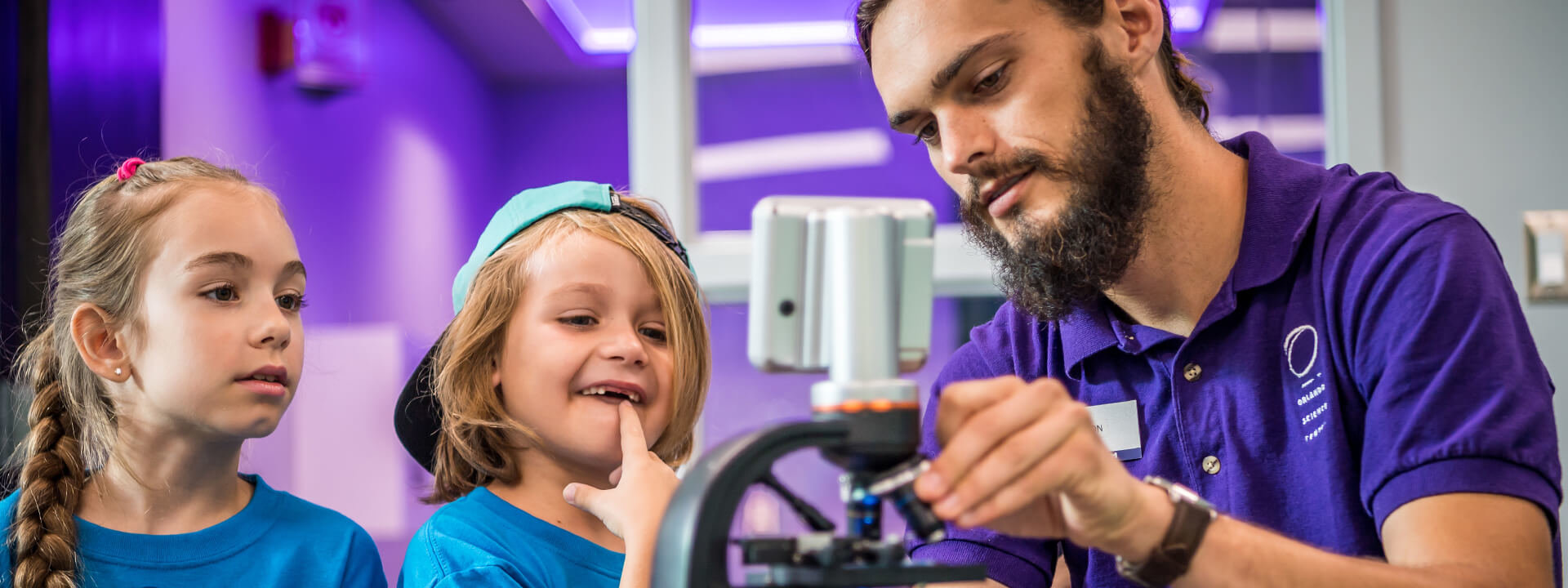 An educator shows two children in summer camp a cell in a microscope.