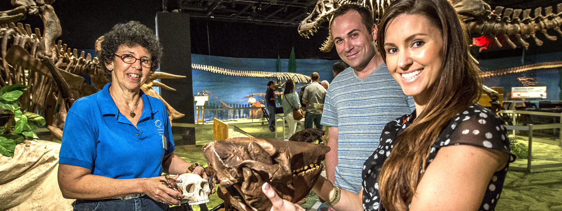 Adult volunteer in the DinoDigs exhibit showing fossils to visitors.