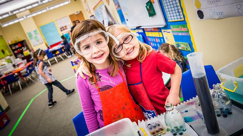 Two children in preschool measure liquids into different containers.