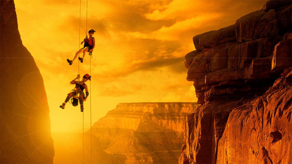 Journey Into Amazing Caves - photo of two climbers descending on ropes.