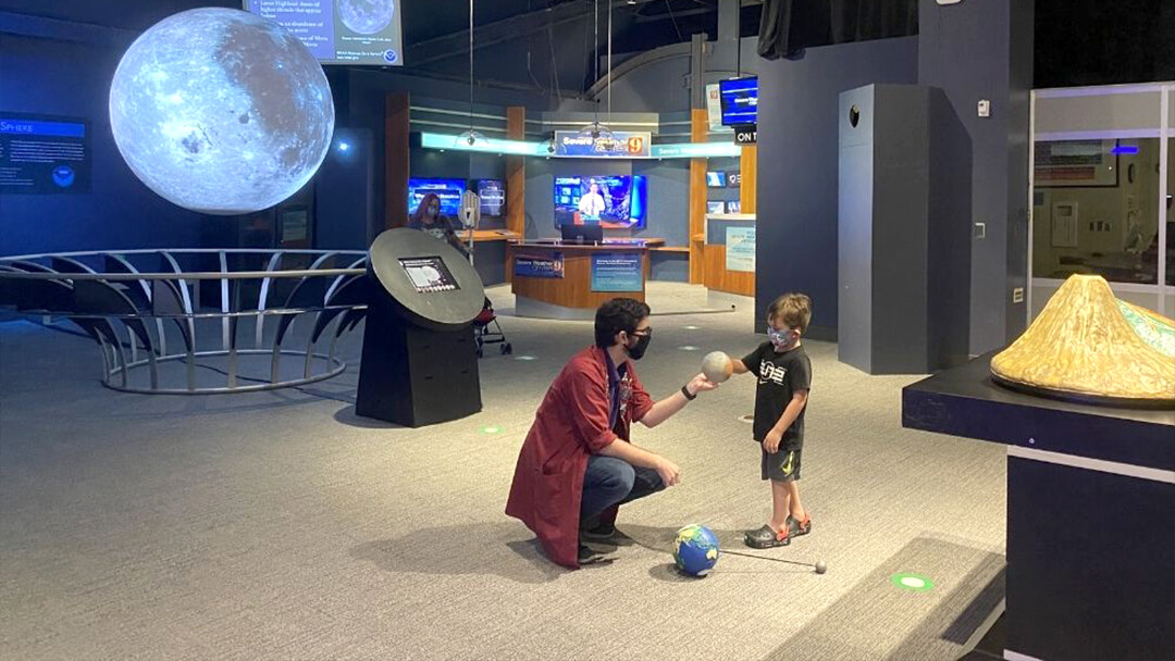 An OSC Science Program Interpreter shows a young child a model of Mars during a Space Tour.