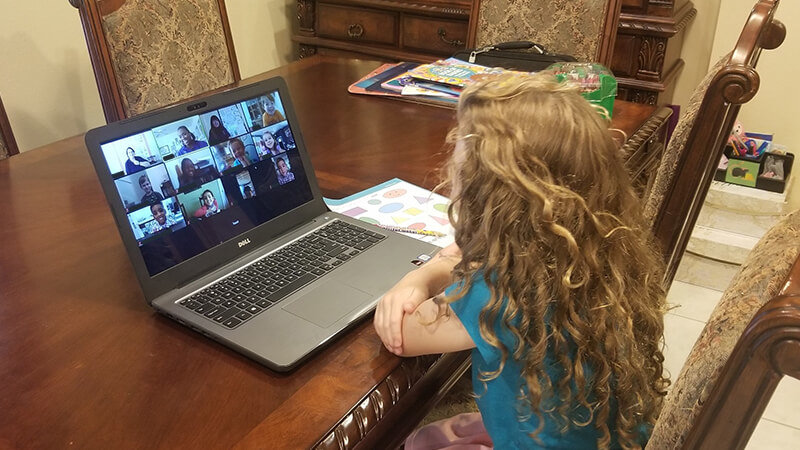 Young child participating in Virtual Preschool Connection on a laptop computer at home.