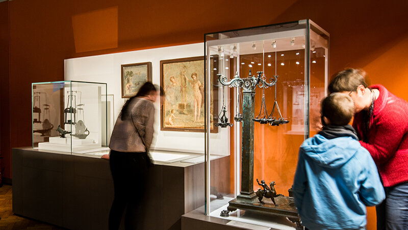 Three people examining glass cases of artifacts in Pompeii: the Immortal City exhibition.