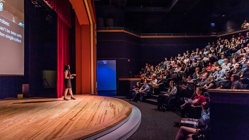 Guests listening to presenter on stage of Digital Adventure Theater.