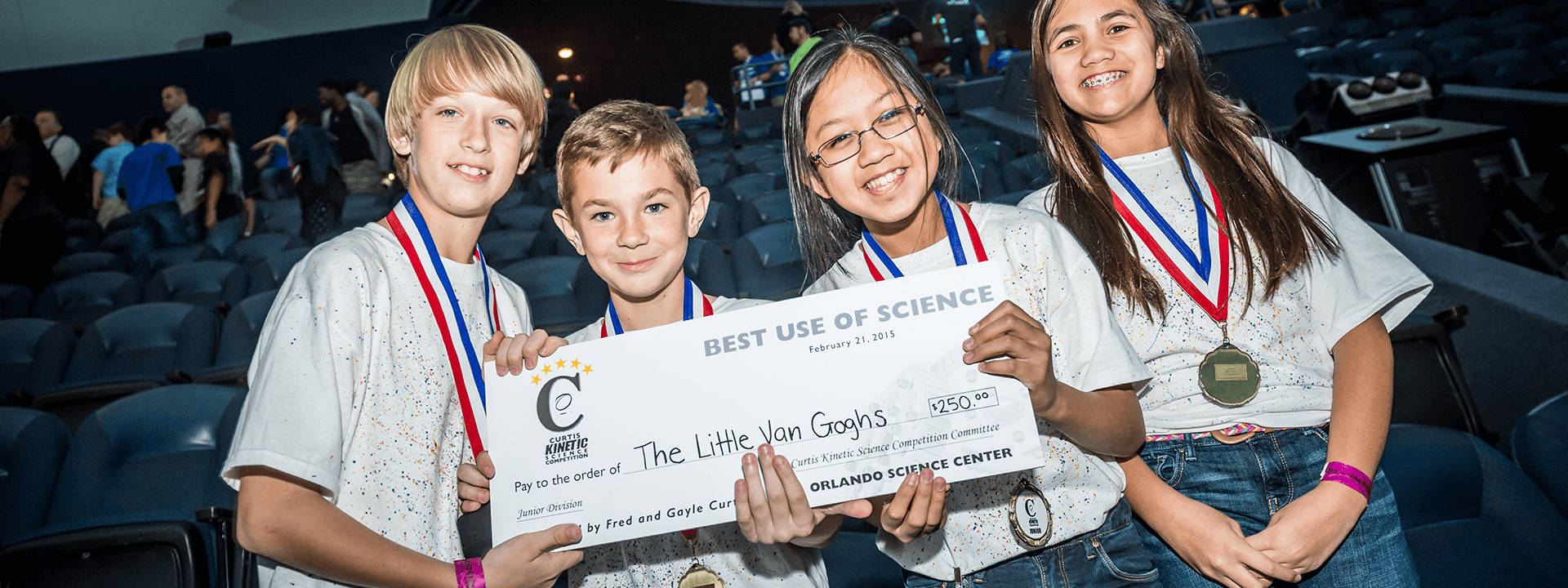 Middle school students display their giant check prize after the Curtis Kinetic Science Competition.