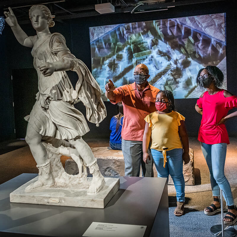 Family group looking at a Pompeii era statue together.