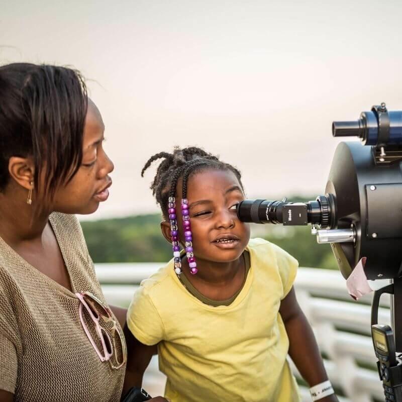 Little girl looking through a telescope