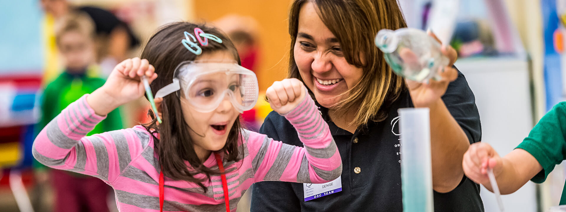 A preschool student shows her excitement during a chemistry experiment.