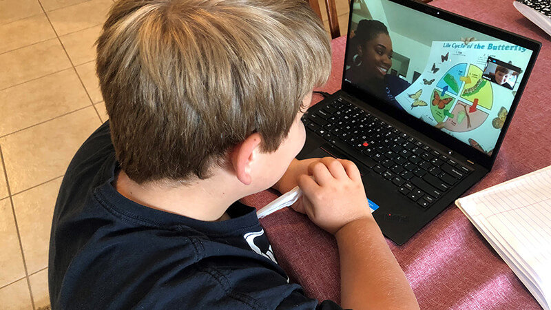 Camper enjoying STEM Virtual Camp at home through laptop interaction with OSC staff.