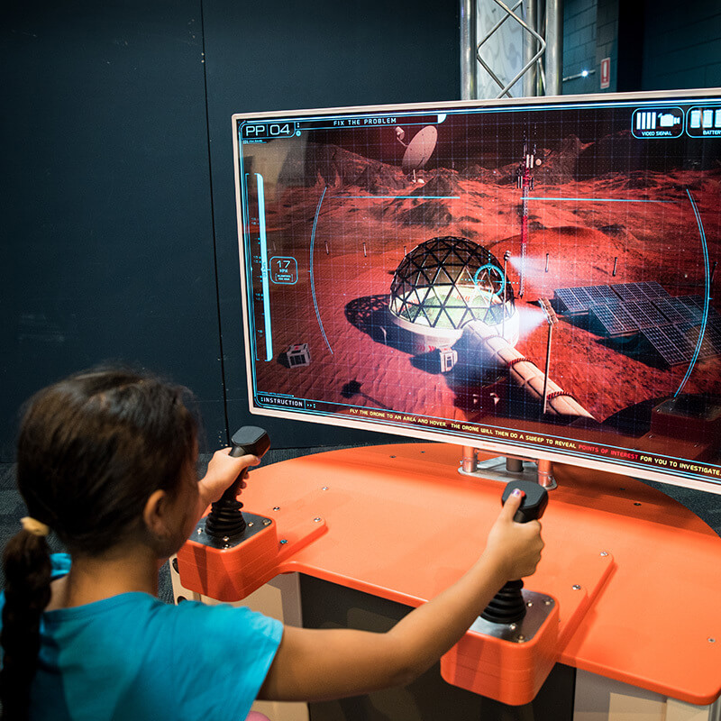 A child building a virtual habitat with gaming controllers