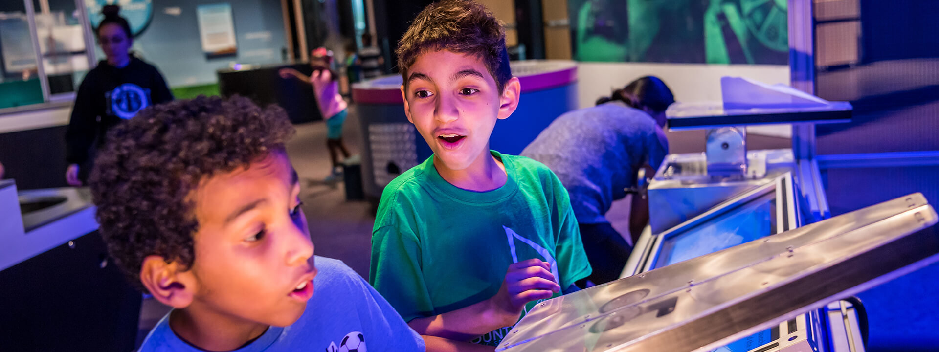 Two boys use the paper airplane launcher in the Our Planet exhibit.