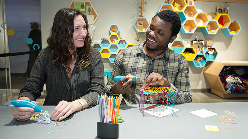 Two guests making crafts together with 3-Doodler pens in The Hive: a Makerspace.