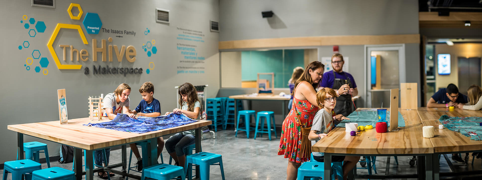 Wide view of several people working at sewing crafts on tables in The Hive.