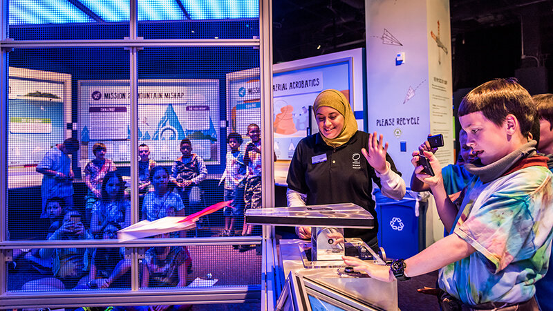 A student uses paper airplane launcher at aviation exhibit while group and instructor looks on in Our Planet exhibit hall.