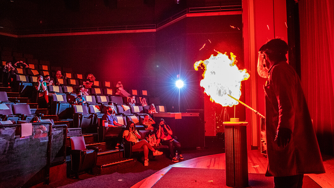 An OSC Science Program Interpreter explodes a balloon of flammable gas on stage during a KABOOM! Live Show