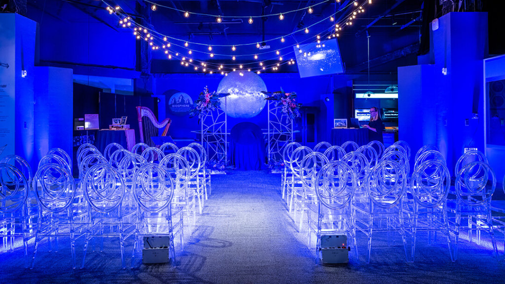 Wedding aisle setup in Our Planet exhibit featuring blue lights and beautiful clear chairs.