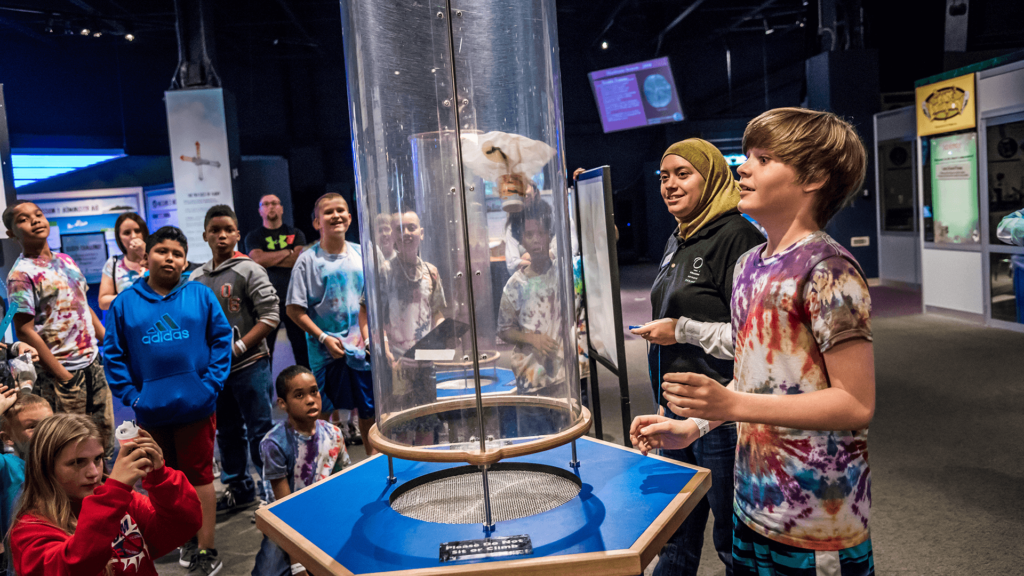 Students do a wind tube engineering activity in the Our Planet exhibit.