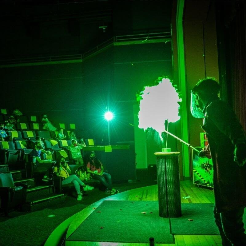 A person creating a green explosion on a stage