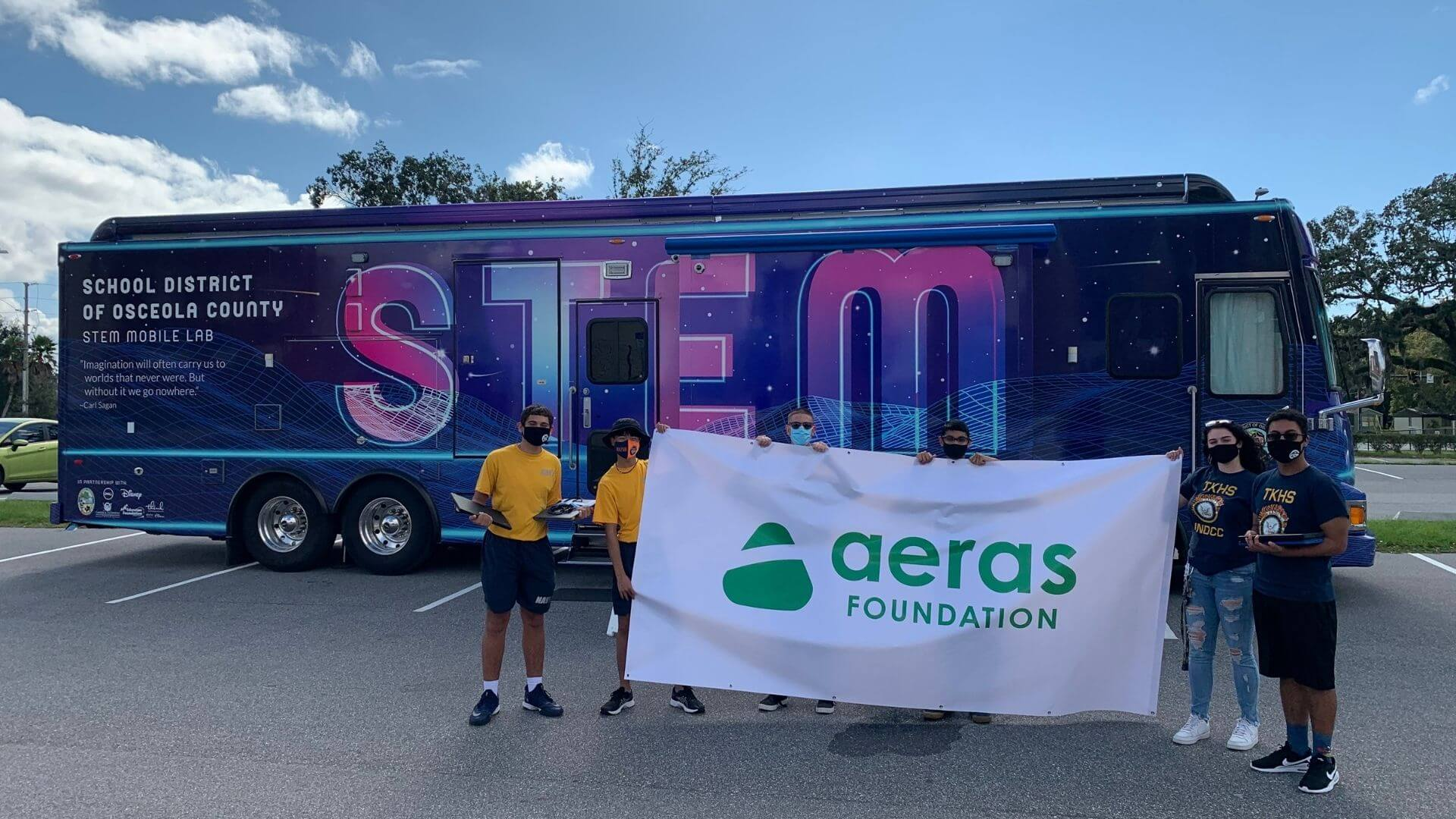 Teens in front of a STEM themed bus holding a banner