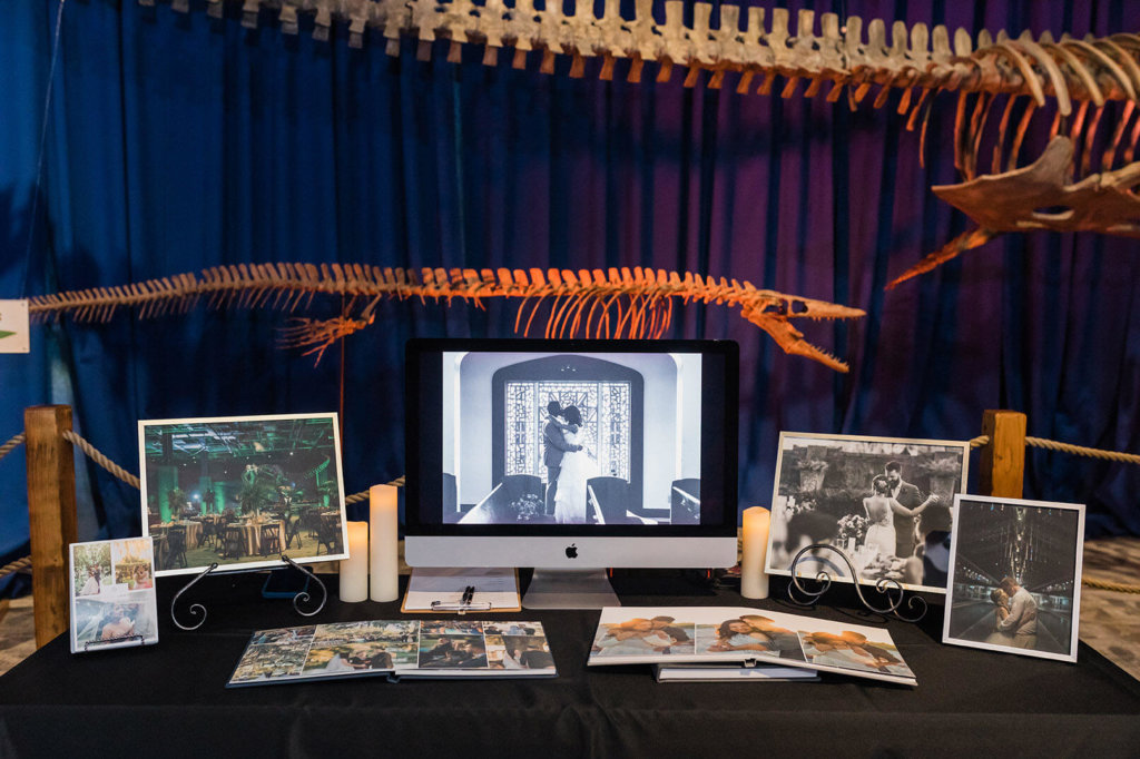 a table of photo books in front of a dinosaur