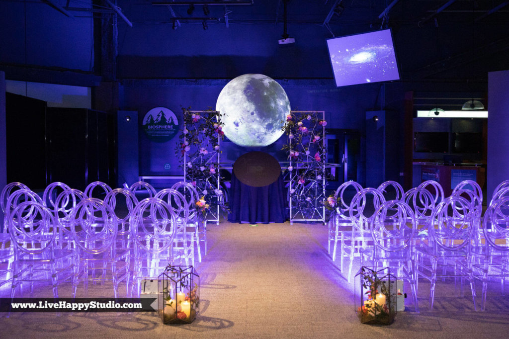 chairs set up for a wedding with purple lighting and a moon backdrop