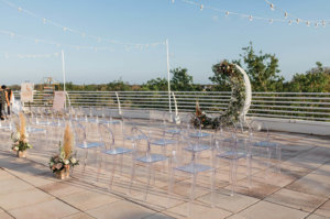 the terrace decorated for a wedding with chairs and a flower sculpture
